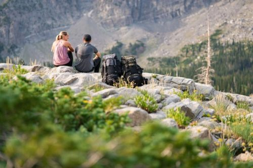 Lifestyle couple sitting on mountains with Teton Sports Explorer 4000 Backpacks