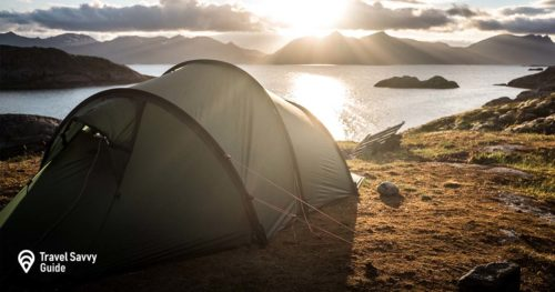 Camping tent at a lake shore with mountain range in background