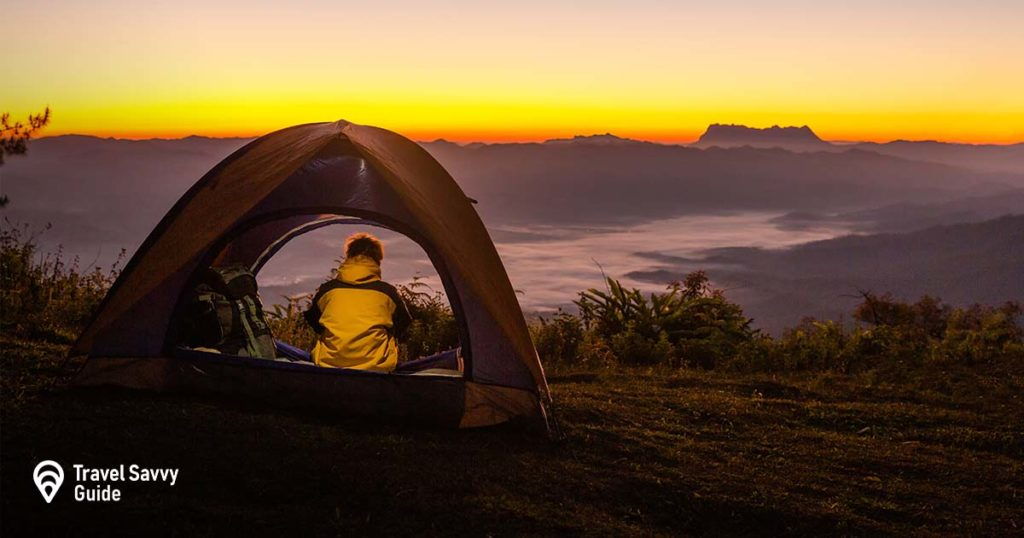 A person sitting in a tent overlooking the mountains