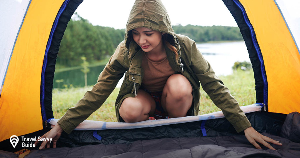 Girl with a rain jacket setting up a tent