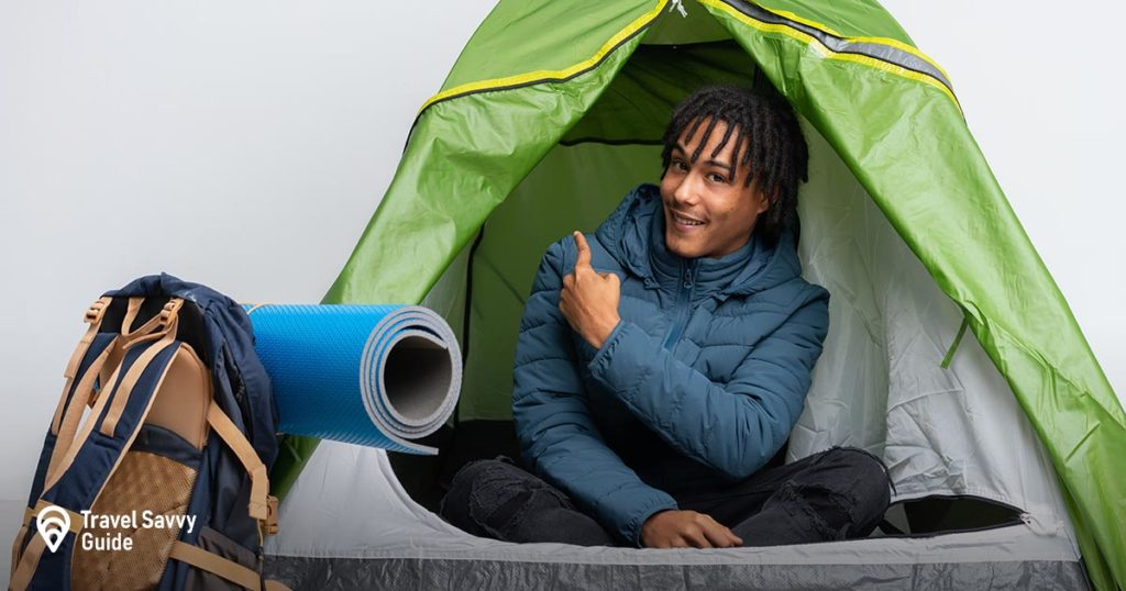 Guy inside a tent with a backpack and mat