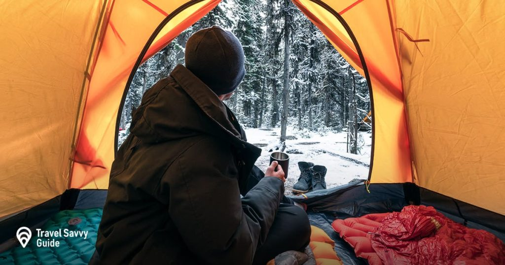 Man drinking water in a tent during winter