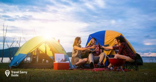 Party at tents, camping of men and women group at forest