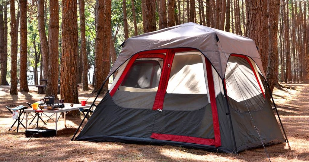Camping tent with desk and chairs in pine forest
