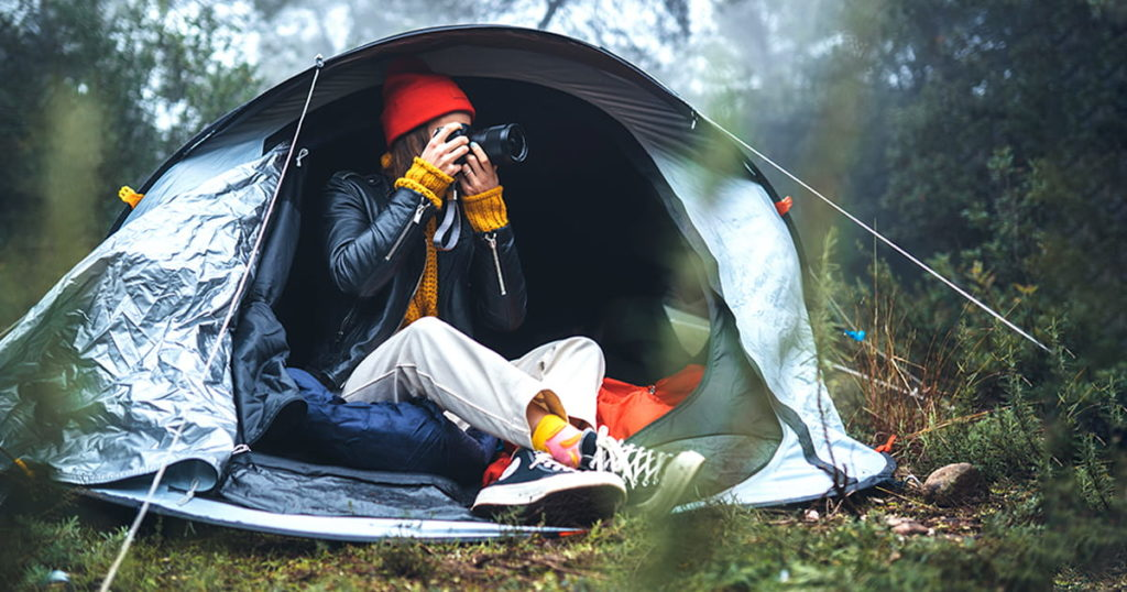 photographer tourist traveler take photo on camera in camp tent in foggy rain forest