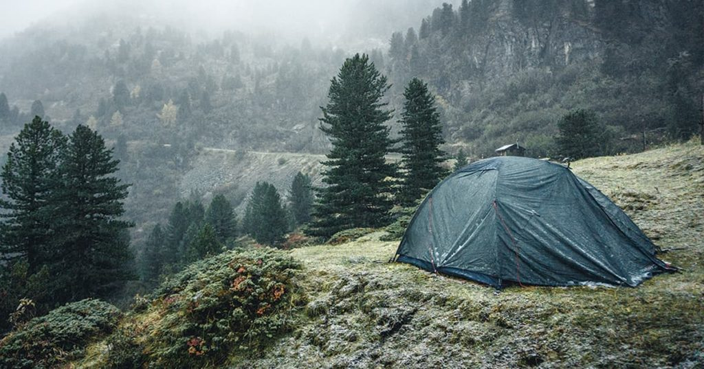 Camping in tent in winter forest