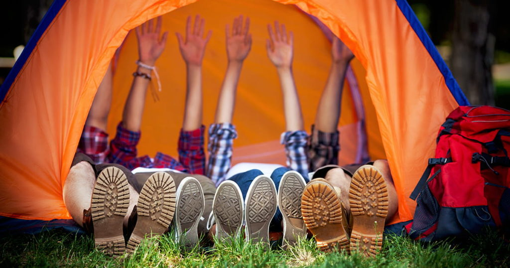 Group of young campers lying down in a tent with their hands up