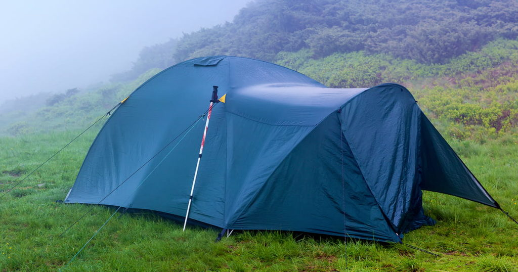 tent after the storm with ajar entrance mounted on the mountain meadow in a heavy fog