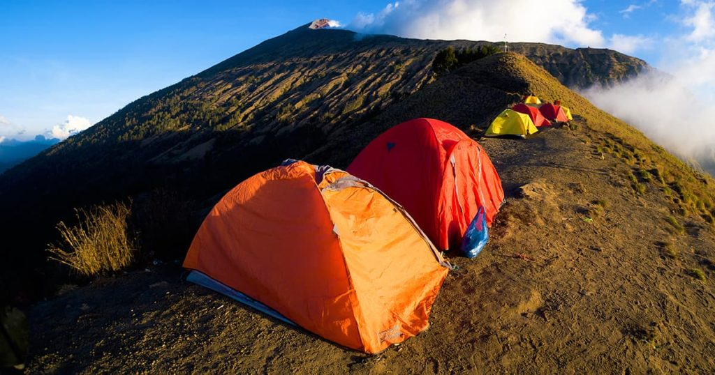 Tents on landscape view of volcano.