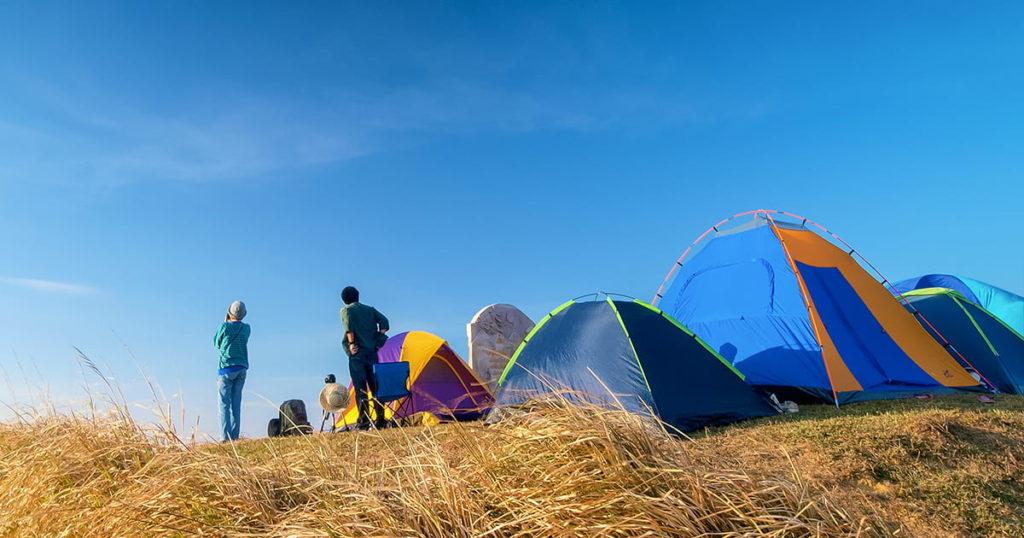 camping tents with tourists standing on top hill