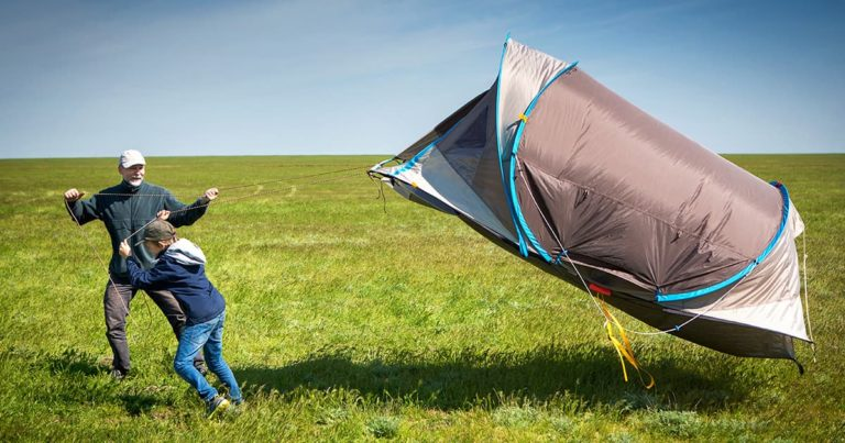 A boy and a man in a vast field with a tent. Tent blows the wind.