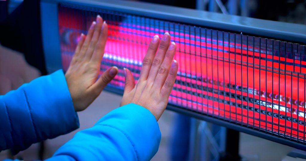 Girl Hands Warming With Heating Radiator at evening winter outdoor