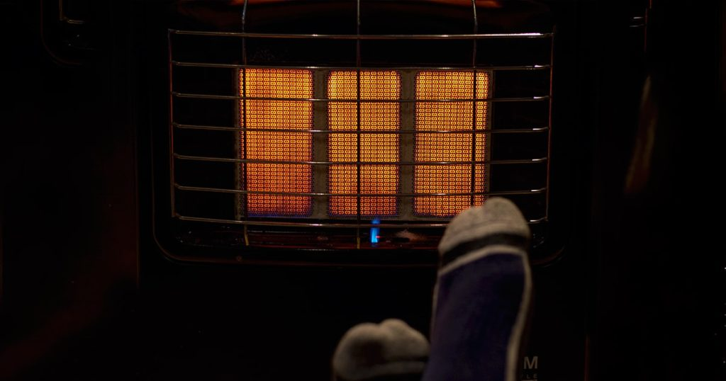 A photo of feet with socks getting some heat from a gas heater on a cold winter night.
