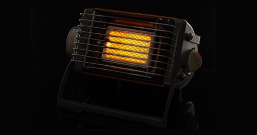Camping portable gas ceramic heater, works and stands on a black glossy background