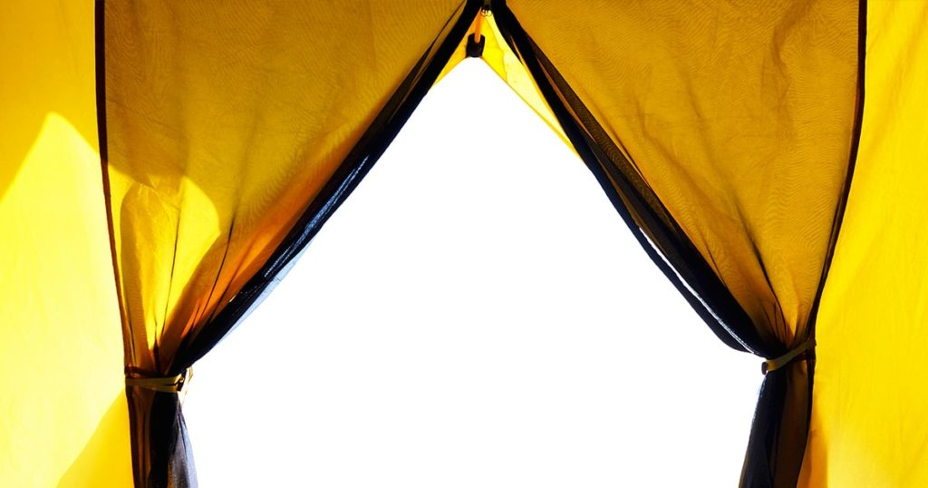 Looking through opening door of yellow tent camping isolated on white background