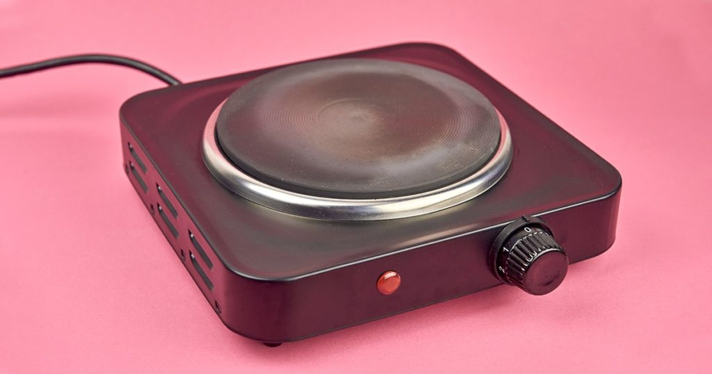 black portable electric stove on pink background