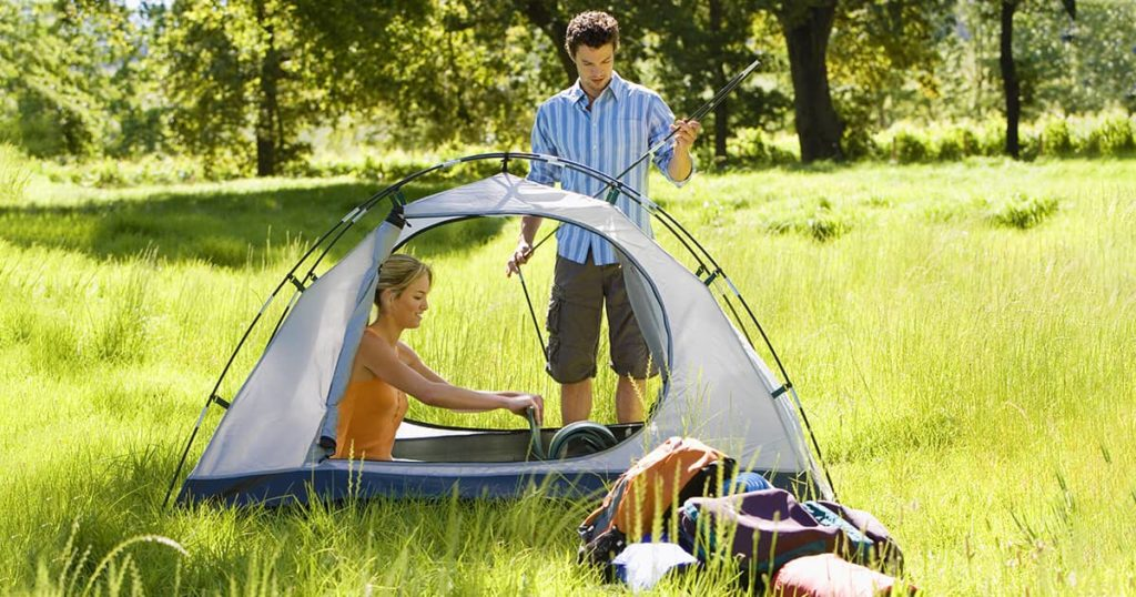 Young couple assembling pop up tent on camping trip