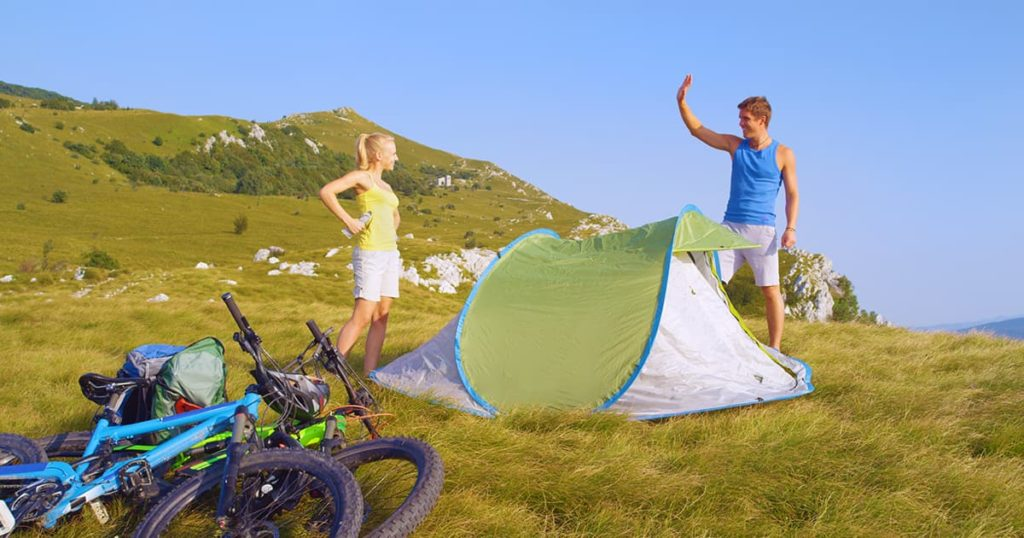 Tourists set up their pop up tent in the middle of the large meadow