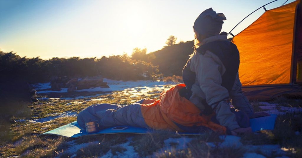 Girl sitting in a sleeping bag on snow