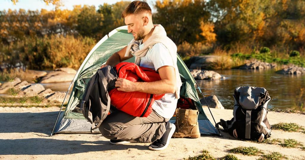 Young man packing sleeping bag near camping tent outdoors