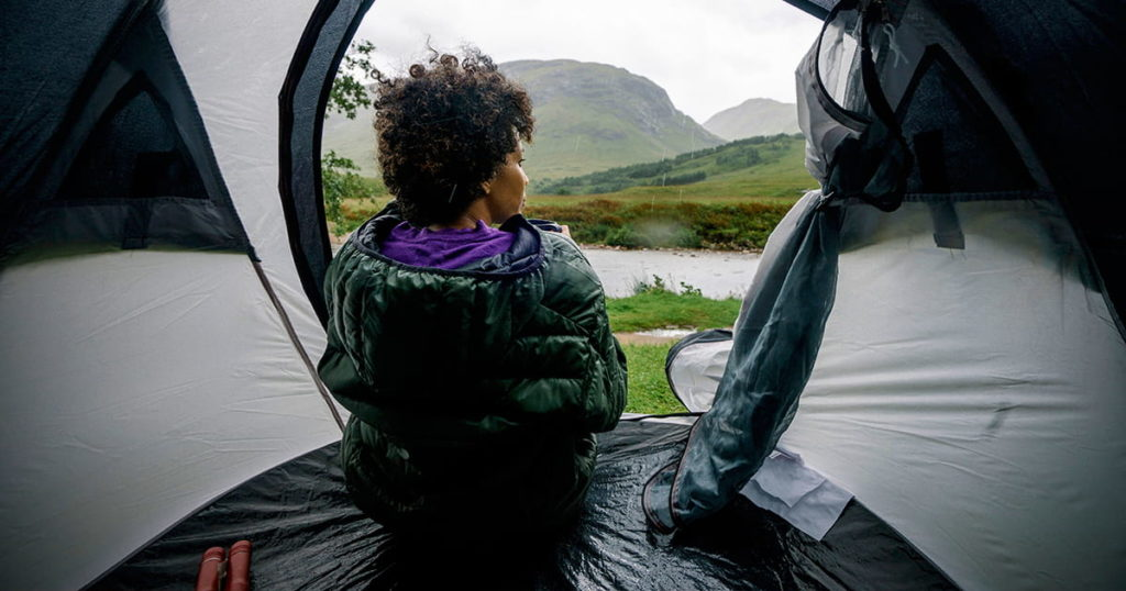 Woman sitting in a tent while it's raining