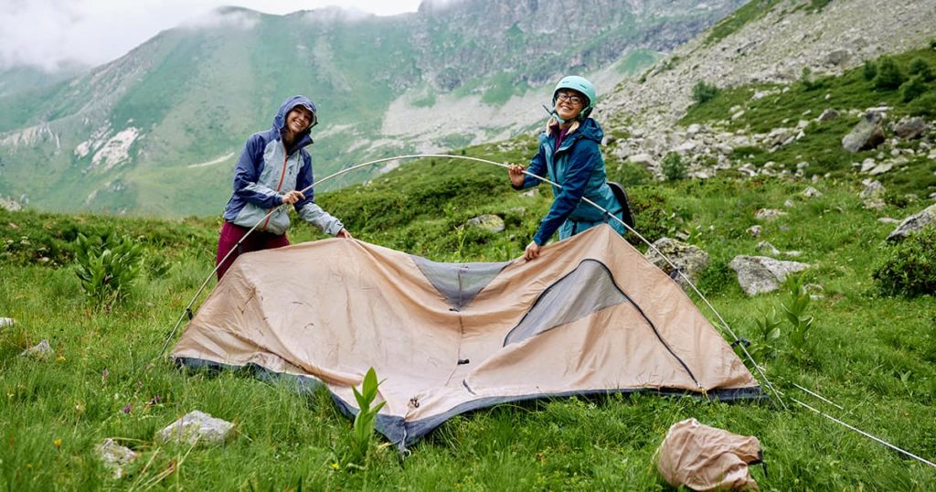 Two young women are setting up the tourist tent