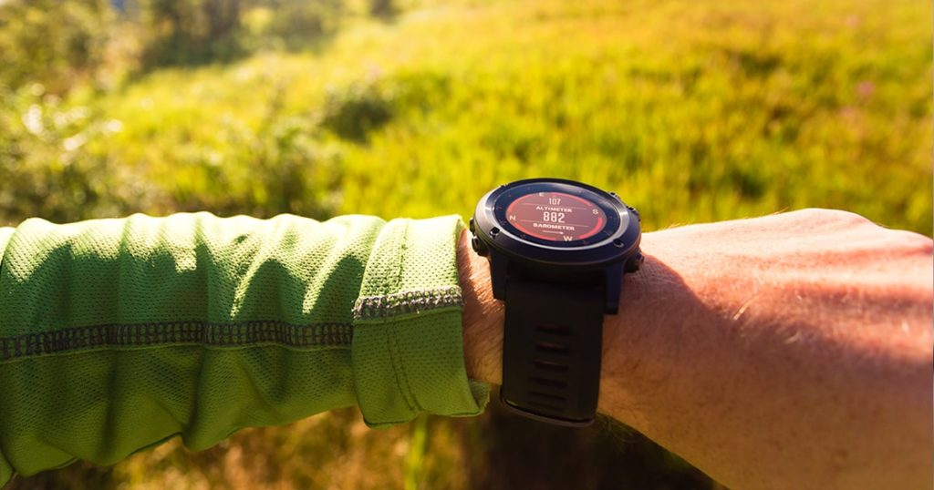 Hiker or traveler on mountain trail checking direction on electronic compass