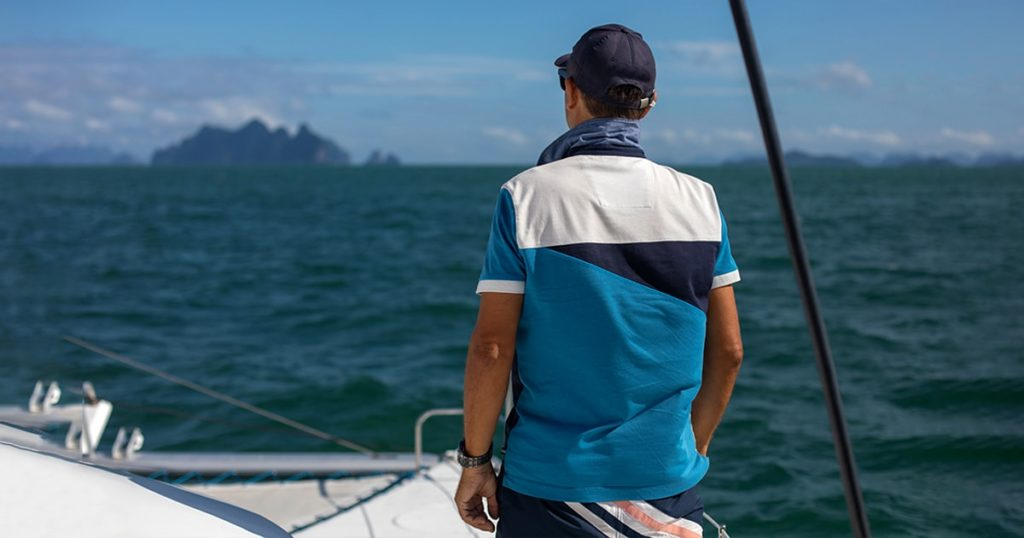 view from behind of sailing man in blue t-shirt and a cap and a wrist watch on hobby boat at sea