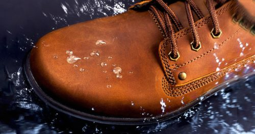 Brown leather boot stepping into water with splash on surface.