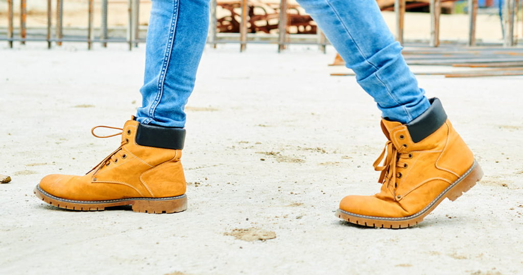 worker wearing jeans and boots crossing construction site