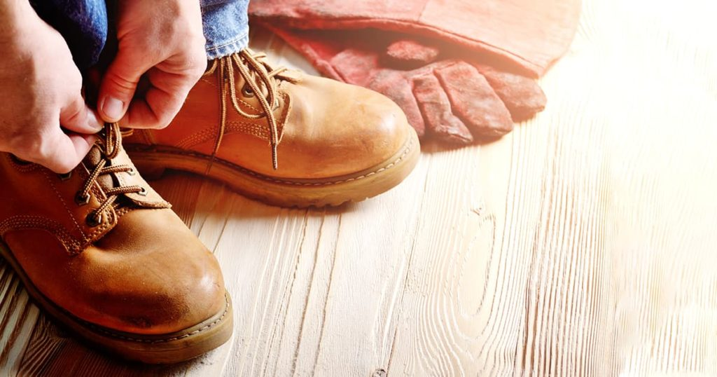 Carpenter in blue jeans tying shoelaces of yellow work boots on on wooden floor.