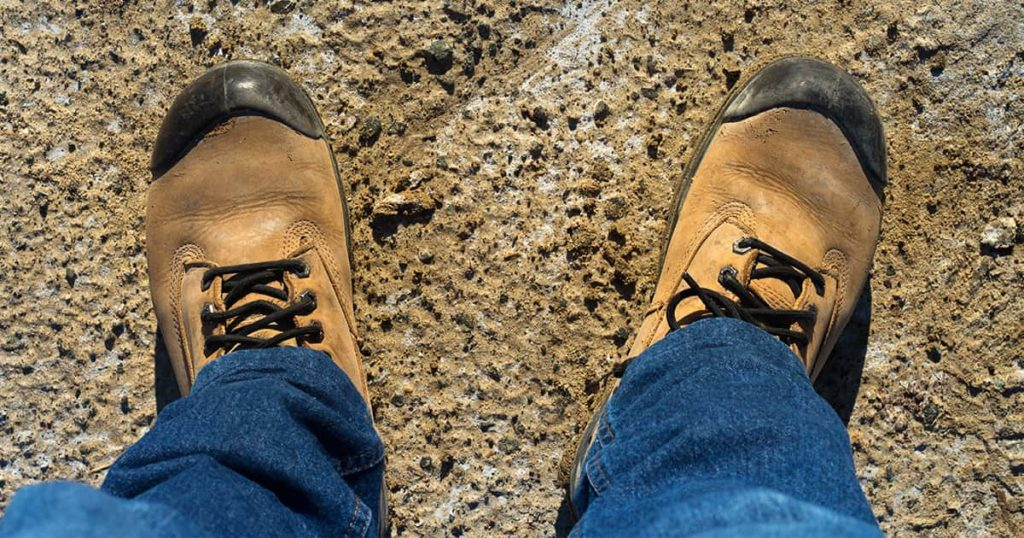 Safety brown boots on work area with construction equipment background