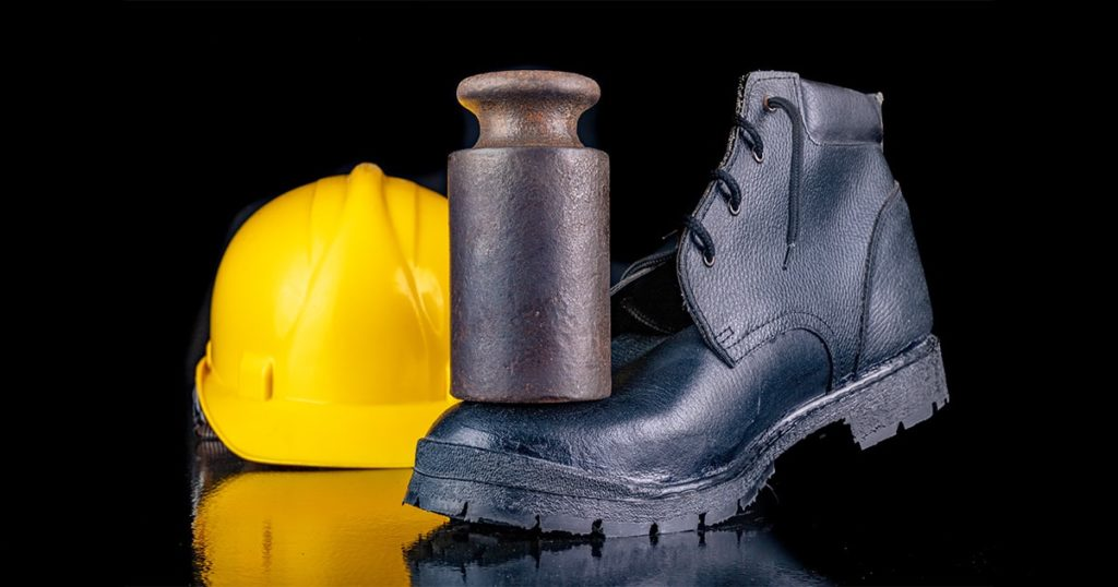 Shoe crushed by a metal weight. Work clothes for construction workers. Dark background.