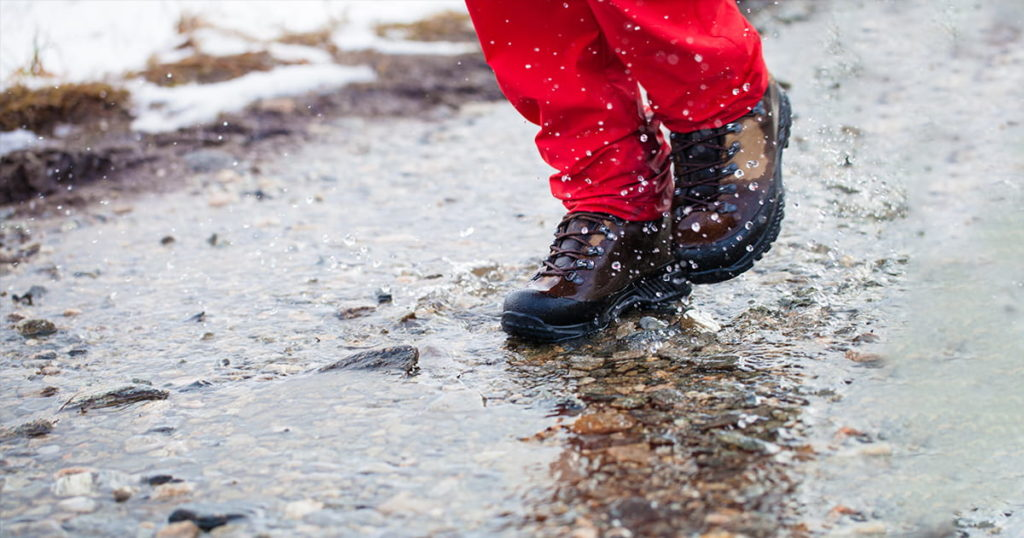 Detail of men's working boots walking through watery footpath