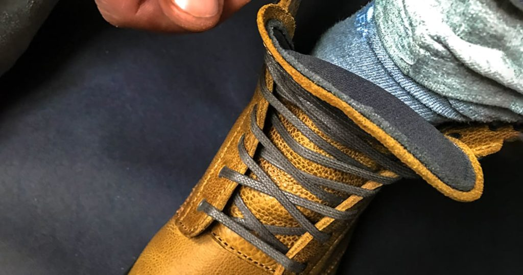 Man putting on yellow shoe and tying shoelaces