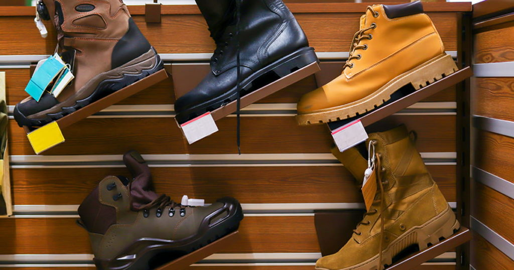 Army boots stand in line at the store counter. Fishing shoes in the store
