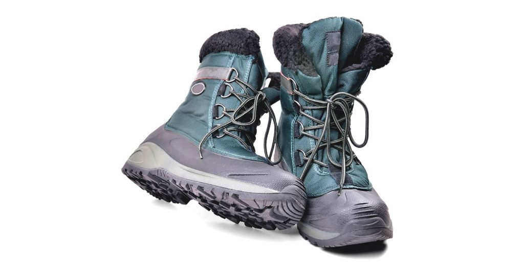 off-road boots insulated for the cold season, high shin, lacing, anti-slip corrugated reinforced sole for travel and winter fishing isolate close-up
