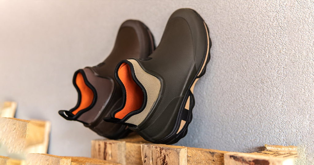 Rubber slip on boots on wooden boards. Shoes for fishing