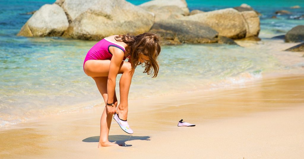 little girl running along the beach in swimming suit