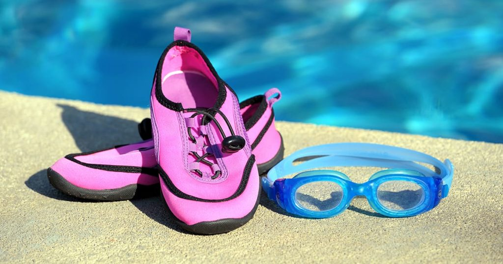 Swimming shoes and goggles in a swimming pool