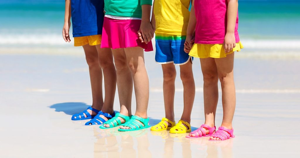 Group of children wearing aqua shoe playing on tropical beach on summer vacation