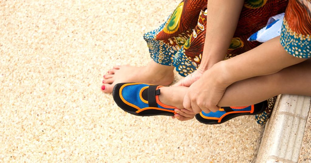 Mother putting colorful aqua shoes for her son get ready to the beach