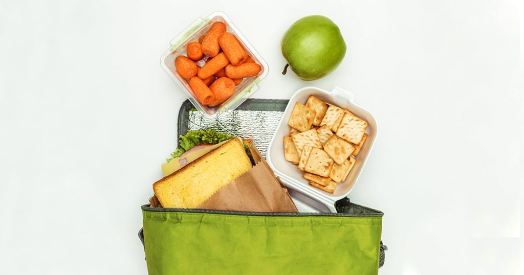 top view of sandwich and carrots with apple in lunch bag isolated on white