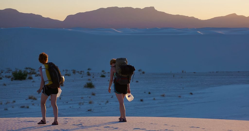 Backpackers hiking into white sands national monument along the gypsum dunes at sunset