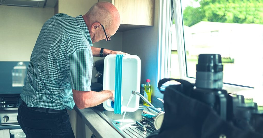 A senior man in a caravan is cleaning a cooler