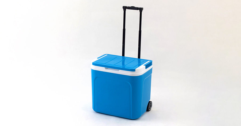Blue cooling box with adjustable handle and wheels isolated on white background