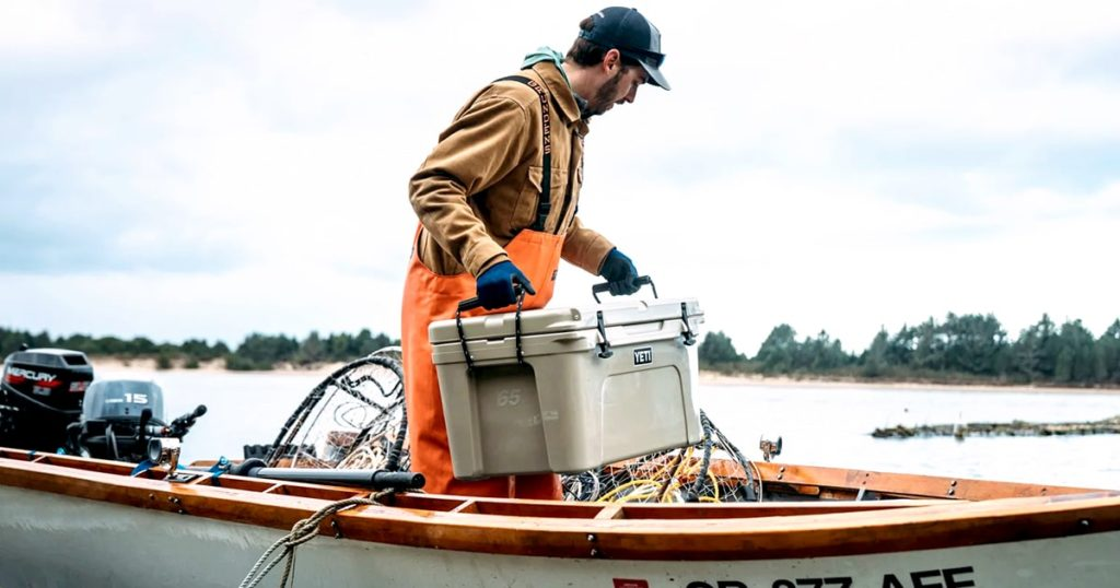 fishermen loading a YETI cooler on the boat