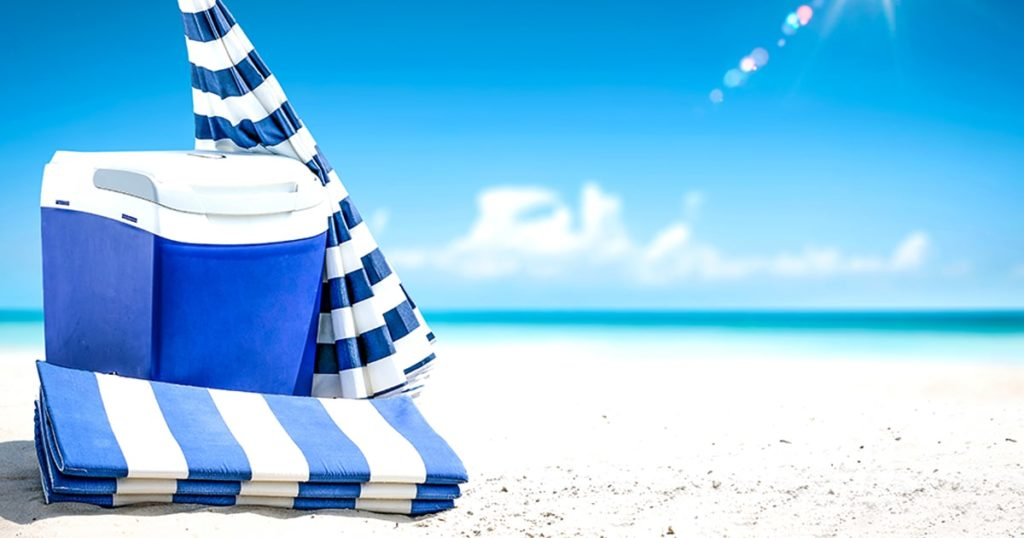 Summer photo of beach and blue beach fridge with umbrella. Sunny day and ocean landscape.