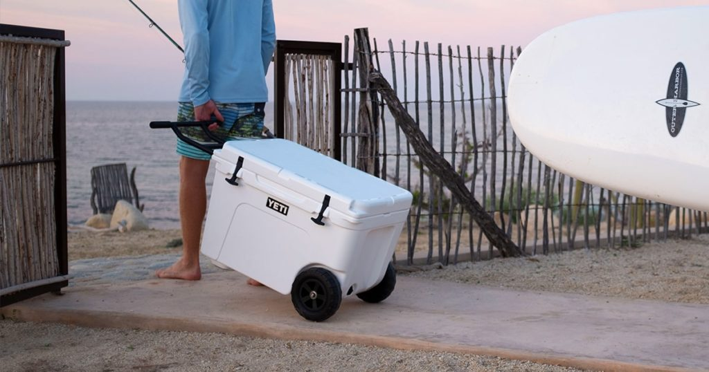 Man carrying a YETI wheeled cooler to be beach