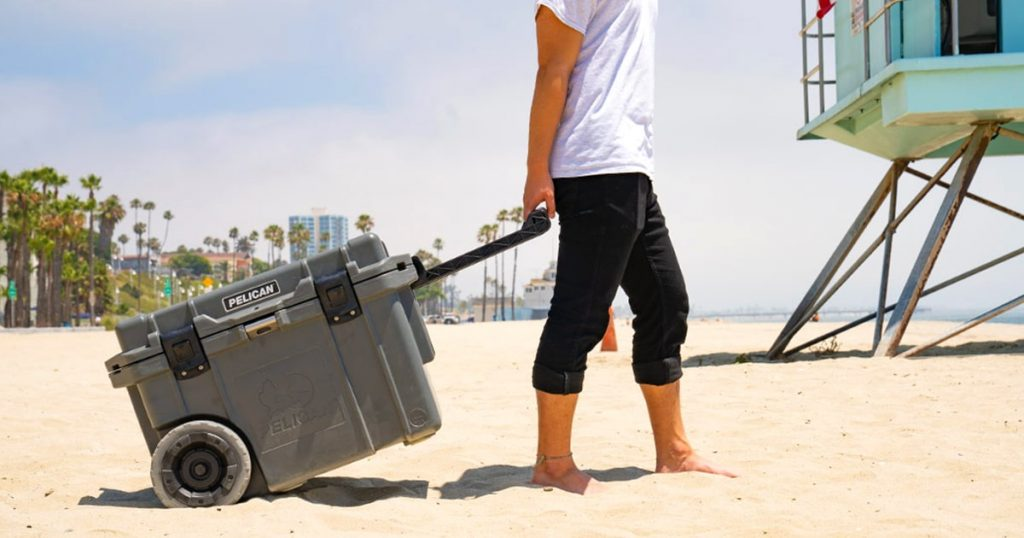 Man carrying a Pelican wheeled hard cooler on the beach